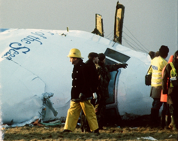 Scottish rescue workers and crash investigators search the area around the cockpit of Pan Am flight 103 in a farmer's field east of Lockerbie Scotland