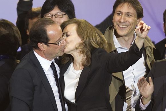 France's newly-elected President Francois Hollande (L) and his companion Valerie Trierweiler kiss as they celebrate