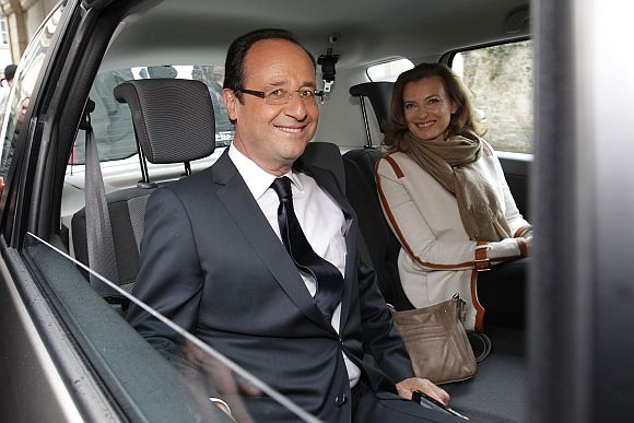 Francois Hollande (L), Socialist Party candidate for the 2012 French presidential election, and his companion Valerie Trierweiler sit in a car