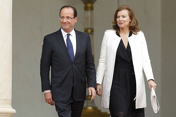 France's new President Francois Hollande (L) and his companion Valerie Trierweiler leave the Elysee Palace after the handover ceremony