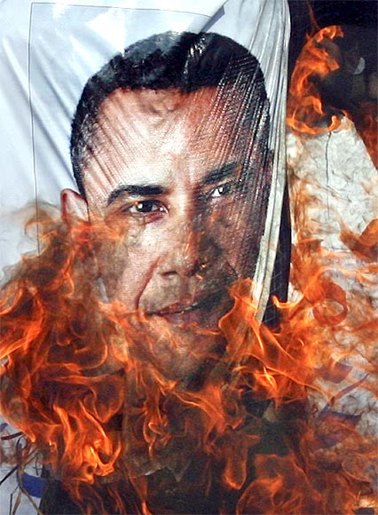 Supporters of the religious political party Sunni Tehreek set ablaze an effigy of US President Barack Obama