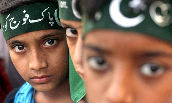 Participants of an anti-America rally wear headbands which read in Urdu 'Salute to Pakistan army'