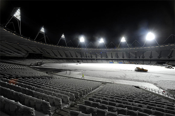 Floodlights illuminate a worker after Britain's Prime Minister David Cameron switched on the floodlights of the Olympic stadium at the Olympic park in Stratford, east London