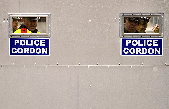 Police officers look through apertures in a mobile steel cordon at the entrance to Whitehall, during a protest march, in central London