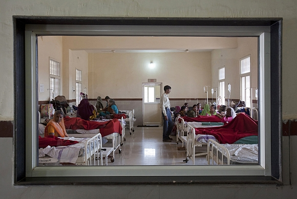 Women who have recently given birth and their relatives are pictured through a nurse's observaton window as they rest in a post delivery ward at a district hospital in Shivpuri, Madhya Pradesh