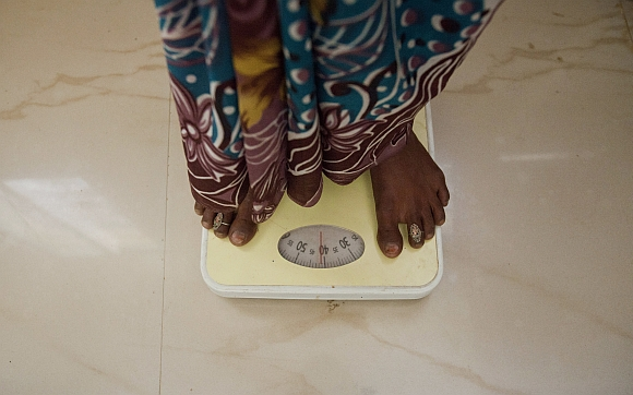 A pregnant woman, stands on a weighing scale during a check up at a community health centre in Chharchh, Madhya Pradesh