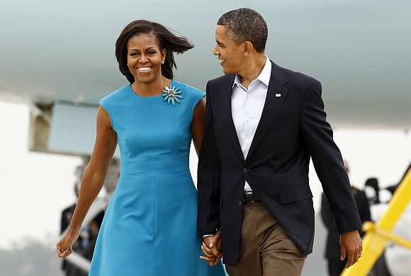 US President Barack Obama and first lady Michelle Obama walk from Air Force One