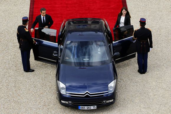 France's outgoing President Nicolas Sarkozy and outgoing First Lady Carla Bruni-Sarkozy leave the Elysee Palace at the end of a handover ceremony in Paris on Tuesday