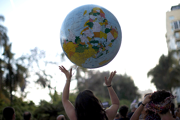 A woman plays with an inflatable balloon of planet earth in Malaga, southern Spain