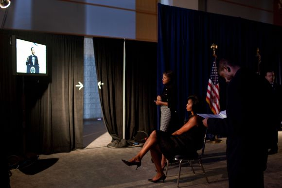 Michelle watches backstage as Obama delivers a speech