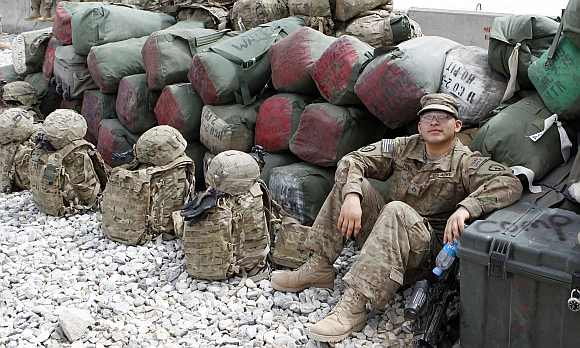 A US army soldier rests among luggage while waiting for a flight to go home after finishing his one year deployment in Afghanistan