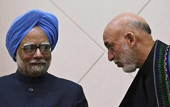 Afghan President Hamid Karzai speaks with Prime Minister Manmohan Singh