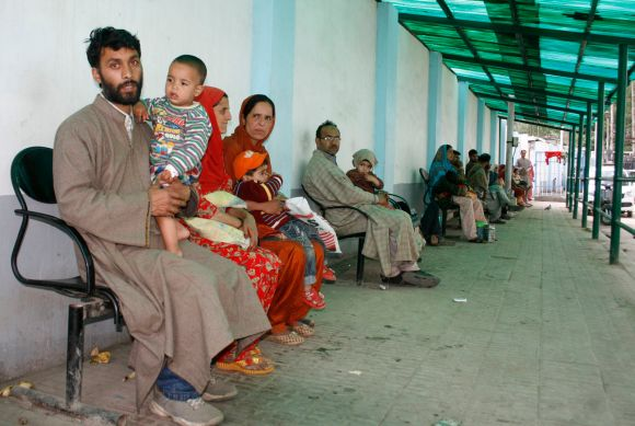 Parents with their children can be seen waiting for doctors at the hospital
