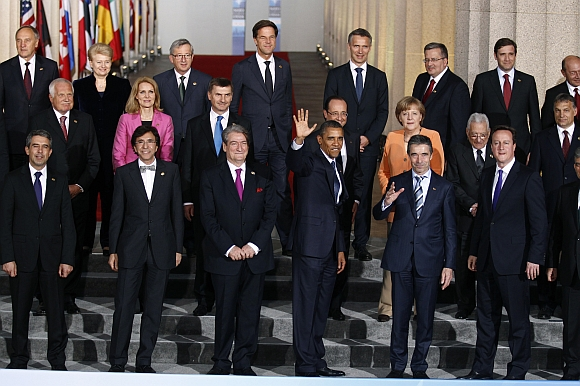 US President Barack Obama waves alongside Secretary General of NATO Anders Fogh Rasmussen as NATO heads of state gather for a family photo at Soldier Field in Chicago
