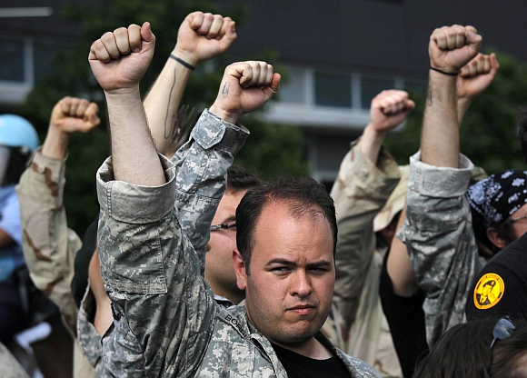 US war veterans raise their hands in solidarity after throwing their medals towards the site of the NATO Summit in Chicago. Nearly 50 veterans threw service medals into the street near the summit site in protest. Baton-swinging police clashed with anti-war protesters marching on the NATO summit in Chicago on Sunday and a lawyers' group representing the demonstrators said at least 12 people were injured, some with head wounds from police batons
