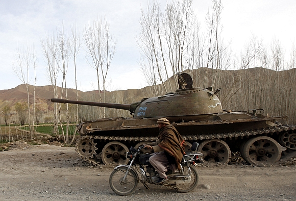 An Afghan man rides a motorcycle past the rusting remains of a Russian tank in Bamiyan province