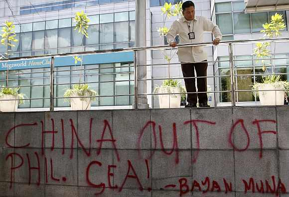 A security guard looks at graffiti done by activists in front of the Chinese consulate demanding the withdrawal of Chinese ships from the disputed Scarborough Shoal in the South China Sea during a protest in Manila's Makati financial district