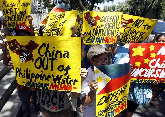 Activists hold placards in front of the Chinese consulate demanding the withdrawal of Chinese ships from the disputed Scarborough Shoal in the South China Sea during a protest in Manila's Makati financial district