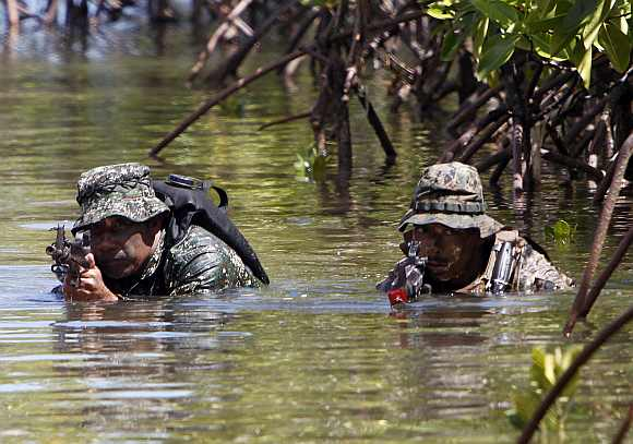 A Philippine and a US marine soldier wade in shallow water in a bay during a amphibious raid as part of a Philippine-US joint military exercise in Ulugan bay, western coast of Philippines