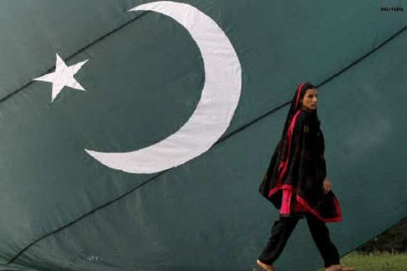 A Pakistani Hindu walks by a giant flag of Pakistan