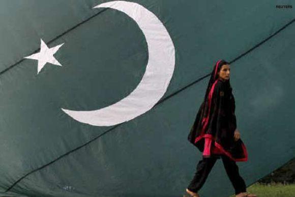 A Pakistani Hindu walks by a giant flag of Pakistan