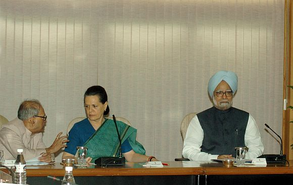 Finance Minister Pranab Mukherjee talks to UPA chairperson Sonia gandhi at the UPA leaders meeting. Also seen is Prime Minister Manmohan Singh