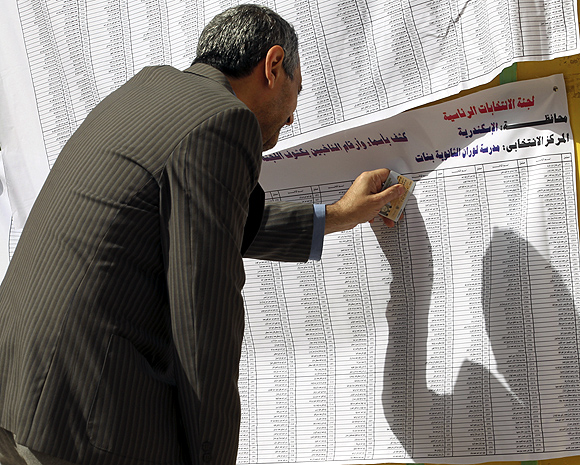 A man looks for his name before casting his vote at a polling station during presidential elections in Alexandria