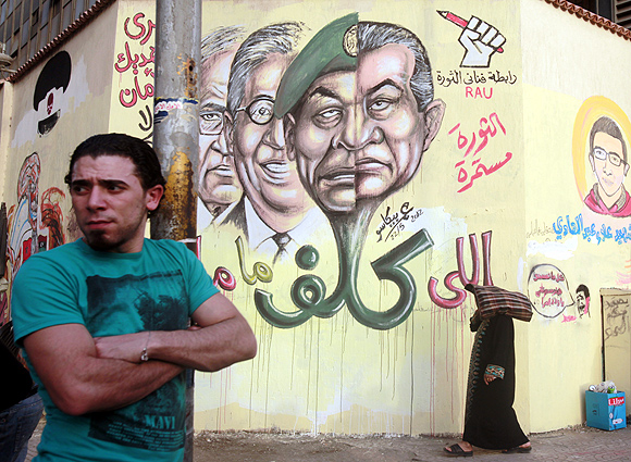 A man stands next to graffiti depicting former President Hosni Mubarak and several presidential candidates, at Tahrir square in Cairo