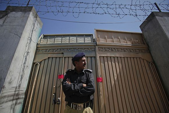 A police officer guards one of two gates of the Abbottabad compound where Al Qaeda leader Osama bin Laden was killed
