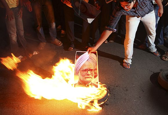 A protester burns a portrait of India's Prime Minister Manmohan Singh during a protest against the proposed rise in petrol prices in Orissa