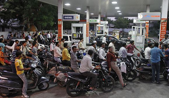 Motorcyclists crowd a fuel station to fill up on petrol in Ahmedabad