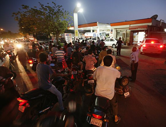 Motorcyclists form a line outside of a fuel station as they queue to fill up on petrol in Ahmedabad