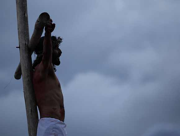 An actor take part in a 'Via Crucis' procession which re-enacts the crucifixion of Jesus Christ