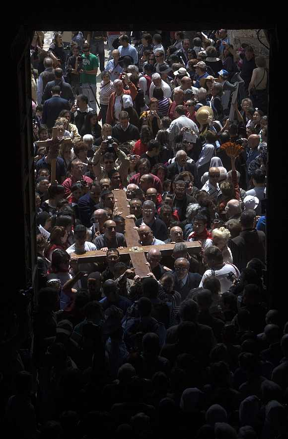 Worshippers carry a cross into the Church of the Holy Sepulcher, also known as the Church of the Resurrection, during the Good Friday procession in Jerusalem's Old City