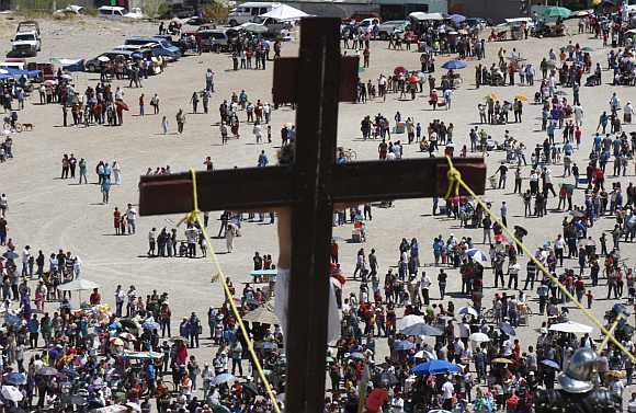 Worshippers stand underneath a hill during a re-enactment of the crucifixion of Jesus Christ on a hill on Good Friday in Ciudad Juarez