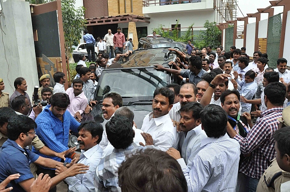 Supporters of Jagan Mohan Reddy surround his vehicle as he arrives at the CBI office in Hyderabad