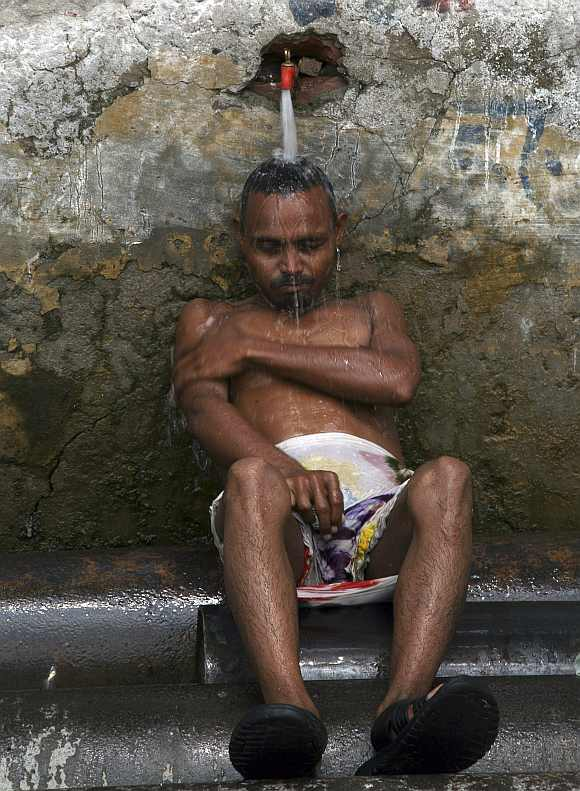 A man cools himself under a tap to beat the heat in Allahabad