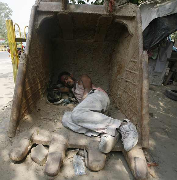 A labourer sleeps inside an excavator bucket on a hot day in Noida, Uttar Pradesh