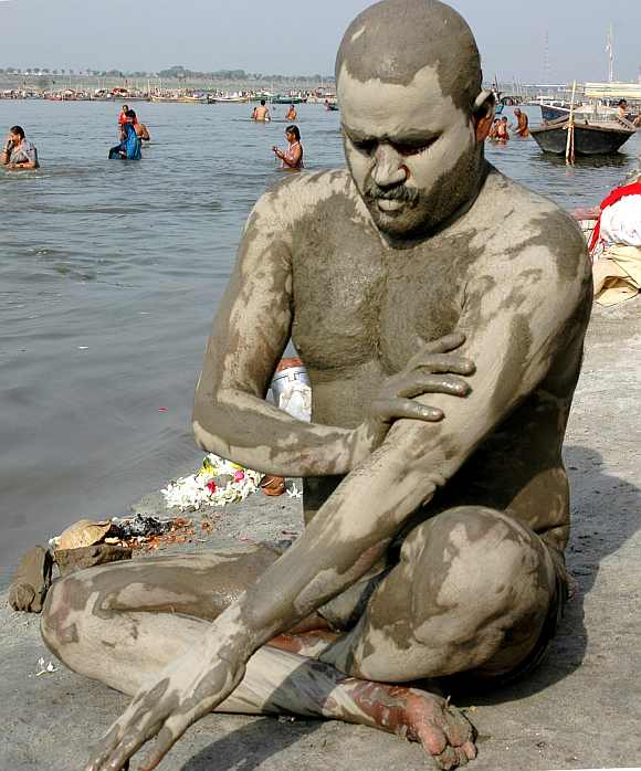 A man cools himself with mud on his body at the Ganges river in Allahabad
