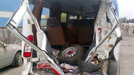 The mangled remains of the tourist minibus, which was hit by a speeding truck on the Mumbai-Pune Expressway