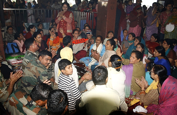 Pilgrims sing devotional songs at the Khir Bhawani Temple