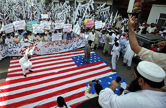 A supporter of the Jamaat-ud-Dawa beats the US flag with his shoes during an anti-American rally in Karachi