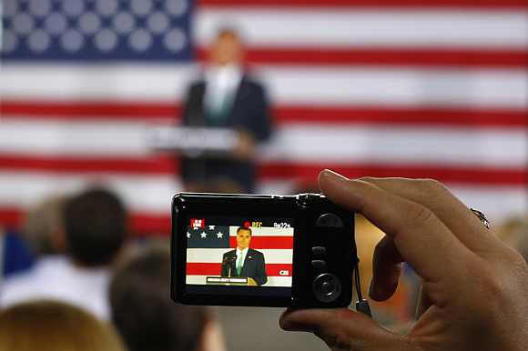 A supporter uses a camera to capture a video of Romney in Charlotte, North Carolina
