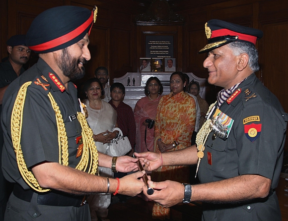 Outgoing army chief General V K Singh hands over the baton to General Bikram Singh