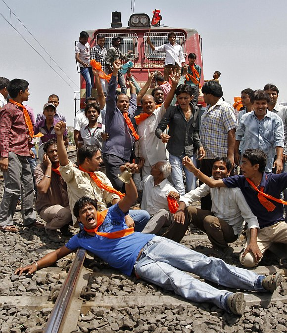 Supporters of the Bharatiya Janata Party shout slogans while blocking a railway track during a protest against a hike in petrol prices in Ahmedabad