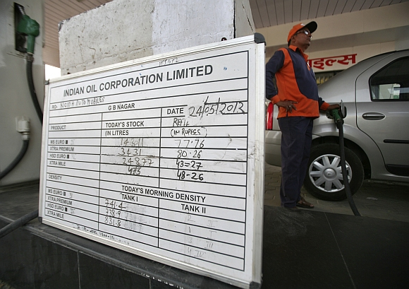 A worker fills a car with petrol next to a price tag board installed at a fuel station in Noida, on the outskirts of New Delhi