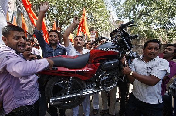 Activists from Shiv Sena carry a motorcycle as they shout slogans during a protest against the price hike in petrol, in Jammu