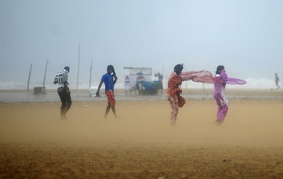 Women shield their faces during strong winds at Marina beach in Chennai
