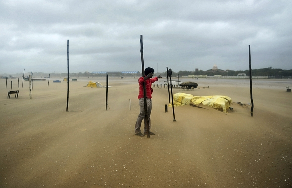 A man holds onto a wooden stick during strong winds at Marina beach in Chennai