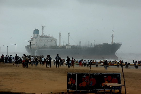 Onlookers watch ship Pratibha Cauvery, which ran aground allegedly due to strong winds, on the bay of Bengal coast, in Chennai